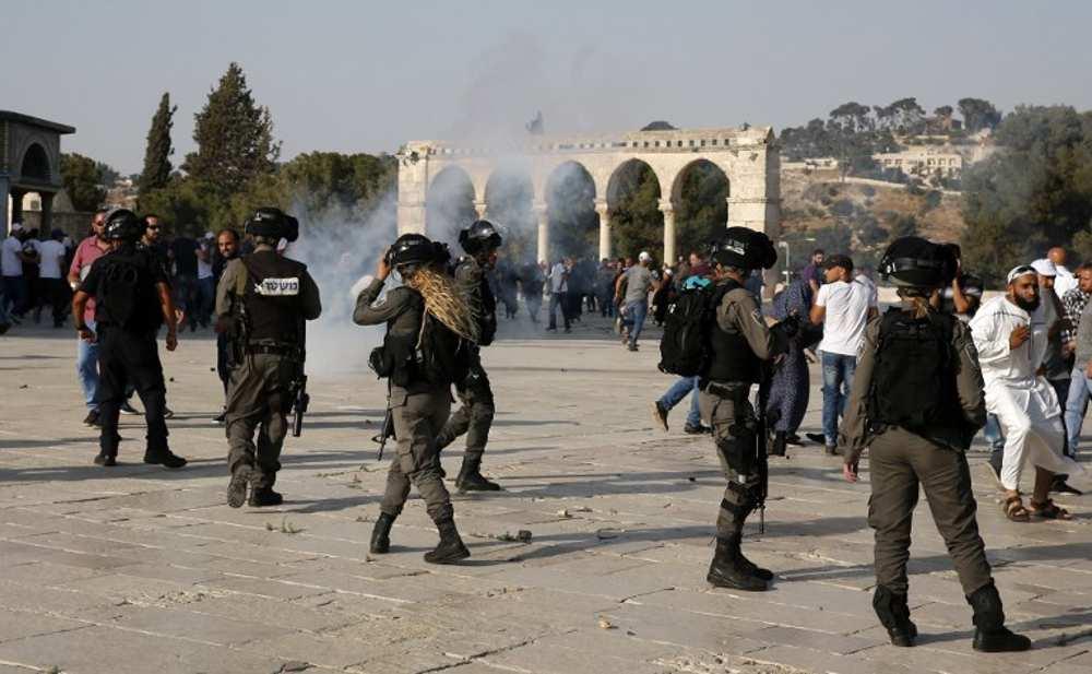 Los humos de gases lacrimógenos se ven en el complejo del Monte del Templo, mientras las fuerzas de seguridad israelíes dispersan a los violentos manifestantes islámicos el 27 de julio de 2017. (AFP Photo / Ahmad Gharabli)
