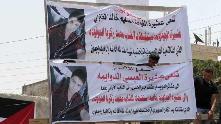 Familiares del terrorista islámico erigen pancartas con el retrato de Mohamed Jawawdeh, quien murió el fin de semana cuando intento asesinar a un guardia de seguridad en el complejo de la embajada israelí en la capital jordana con un destornillador, durante su funeral en Amman el 25 de julio de 2017 (Khalil Mazraawi / AFP)