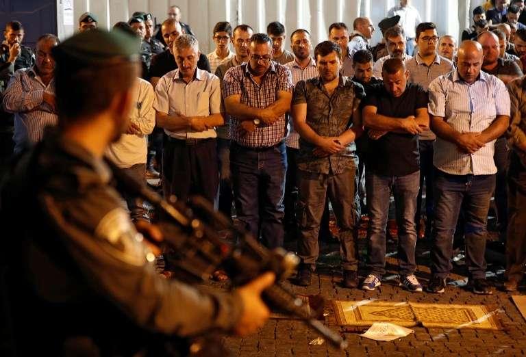 Las fuerzas de seguridad israelíes están de pie frente a los musulmanes que rezan fuera de la Puerta de los Leones, una entrada principal al recinto del Monte del Templo en la Ciudad Vieja de Jerusalémn, el 19 de julio de 2017 (AFP PHOTO / Ahmad GHARABLI)