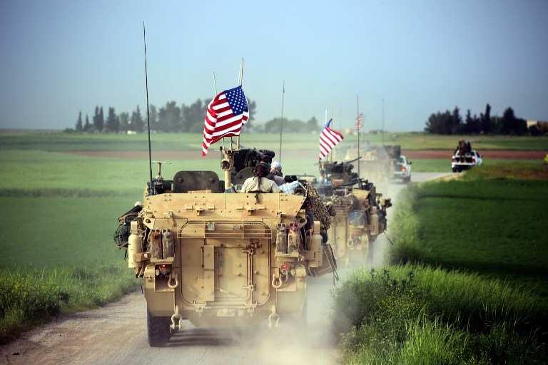 Las fuerzas estadounidenses, acompañadas por combatientes de las Unidades de Protección del Pueblo Kurdo (YPG por sus siglas en inglés), conducen sus vehículos blindados cerca de la aldea siria del norte de Darbasiya el 28 de abril de 2017. (AFP / Delil Souleiman)