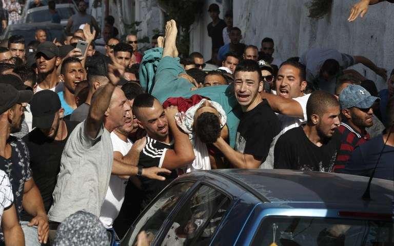 Los hombres árabes trasladan el cuerpo de Mohammed Abu Ghanem, quien murió durante los disturbios violentos contra las fuerzas israelíes, durante su entierro en la zona A-Tur de Jerusalém, el 21 de julio de 2017. (AFP / Ahmad Gharabli)