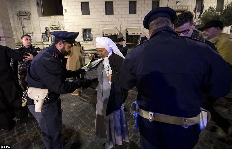 """La policía inspecciona a una monja antes de su ingreso a la """"Plaza de San Pedro"""". (Foto: EPA / www.dailymail.co.uk)"""