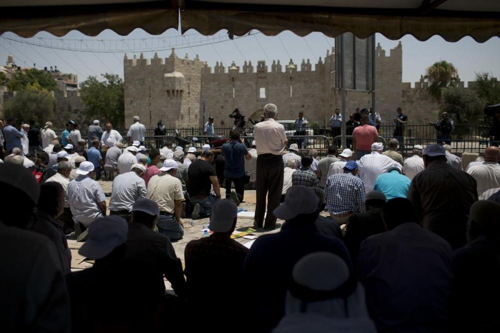 Los musulmanes se reúnen para la oración del viernes fuera de la Ciudad Vieja de Jerusalém, el viernes 14 de julio de 2017. El Monte del Templo fue temporalmente cerrado después de que dos oficiales fueron asesinados por tres terroristas musulmane.(Foto de AP / Oded Balilty)