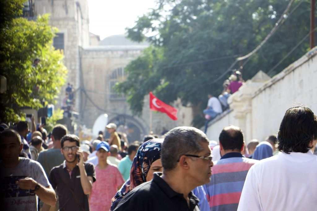 Los musulmanes en la Puerta de los Leones que se negaron a entrar en el Monte del Templo el 27 de julio de 2017, incluso después de que miles comenzaron ingresar. Un manifestante agita una bandera turca. (Dov Lieber / Times of Israel)