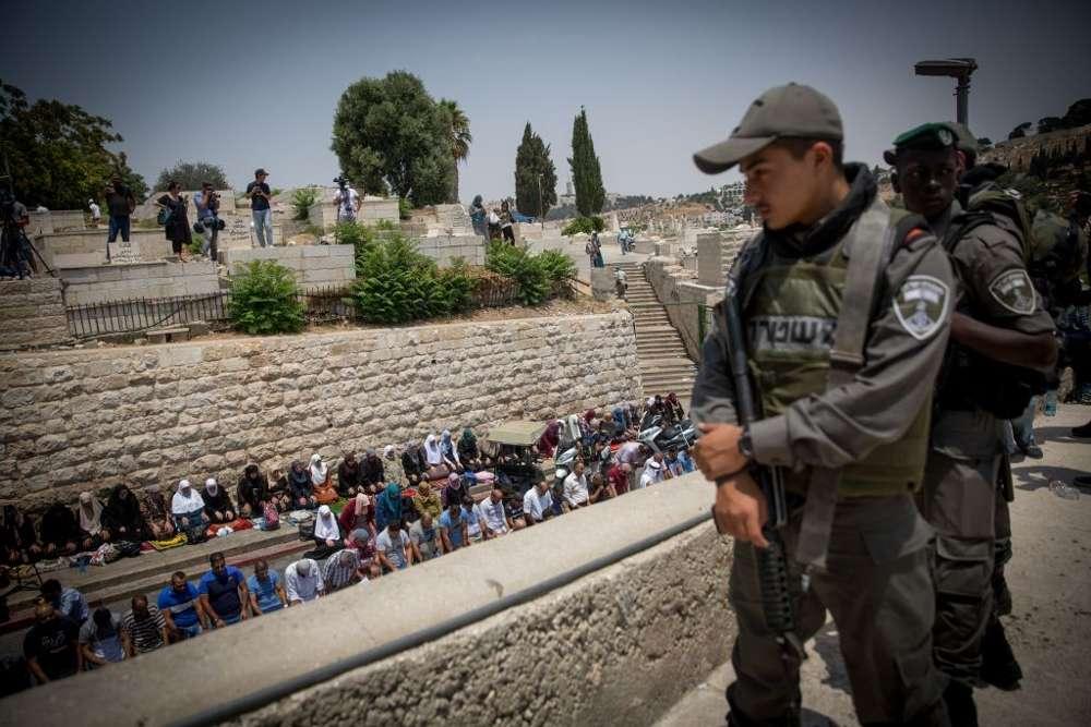 Musulmanes realizan oraciones del mediodía por la Puerta de los Leones, fuera del Monte del Templo, en la Ciudad Vieja de Jerusalém, el 20 de julio de 2017. (Miriam Alster / Flash90)