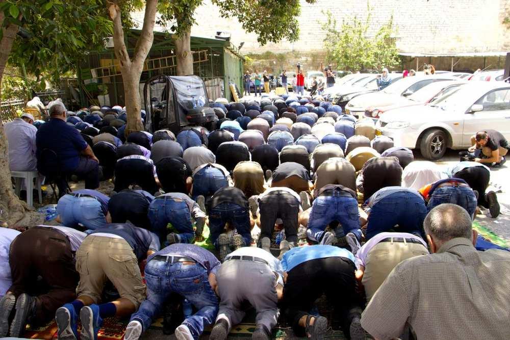 Musulmanes participan en las oraciones del mediodía en un estacionamiento cerca de la Puerta de los Leones en la Ciudad Vieja de Jerusalém, negándose a entrar en el recinto del Monte del Templo para llegar a la Mezquita de Al-Aqsa el 25 de julio de 2017. (Dov Lieber / Times of Israel)