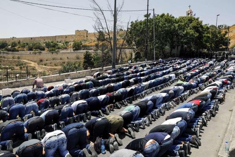 Musulmanes rezan fuera de la Ciudad Vieja de Jerusalém cerca de la Puerta de los Leones el 28 de julio de 2017. (AFP PHOTO / MENAHEM KAHANA)