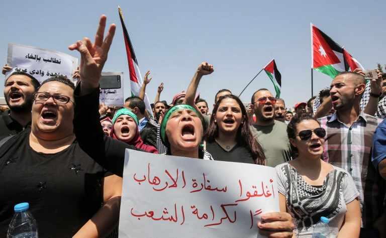 Los manifestantes jordanos agitan las banderas nacionales y cantan consignas durante una manifestación cerca de la embajada israelí en Amman el 28 de julio de 2017, pidiendo el cierre de la embajada, la expulsión del embajador y la cancelación del tratado de paz de 1994 con Israel. (AFP PHOTO / KHALIL MAZRAAWI)