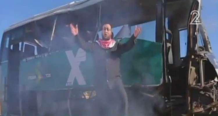 Una imagen fija de un video de Hamas alabando los atentados suicidas lanzados el 7 de febrero de 2016 muestra a un miembro del grupo de pie frente a un autobús israelí quemado (captura de pantalla: YouTube)