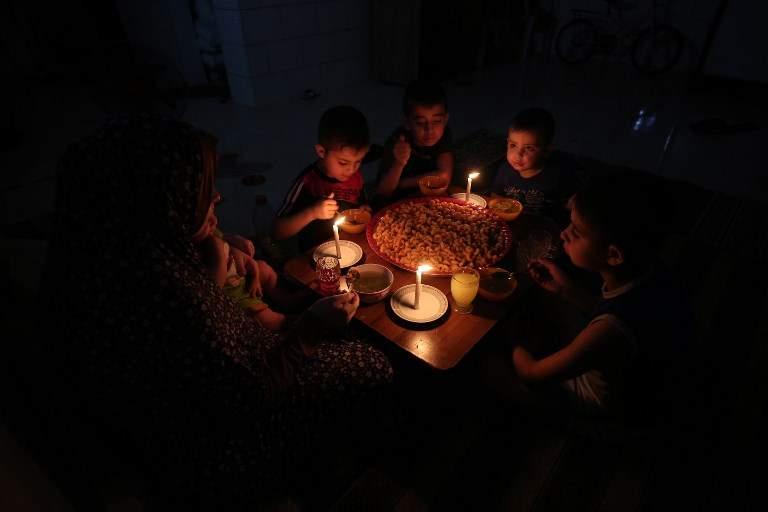 Una familia árabe come cena a la luz de las velas en su casa improvisada en Rafah, en el sur de la Franja de Gaza, durante un corte de energía el 11 de junio de 2017. (AFP / SAIDA KHATIB)