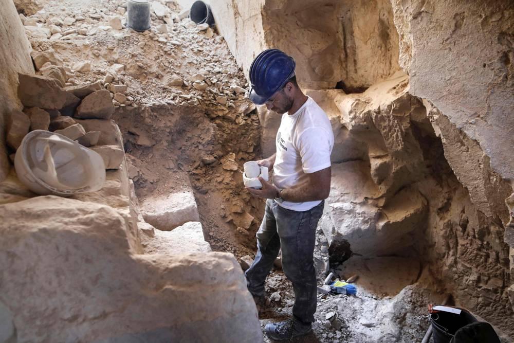 El arqueólogo israelí Yonatan Adler, director de excavaciones en el sitio, inspecciona tazones y núcleos de calcárea del sitio. MENAHEM KAHANA / AFP