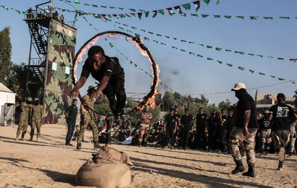 Jóvenes árabes saltan a través de un anillo de fuego durante una ceremonia militar de graduación en un campamento de verano de Hamas en Khan Yunis, en el sur de la Franja de Gaza, el 18 de agosto de 2017. (AFP PHOTO / SAID KHATIB)