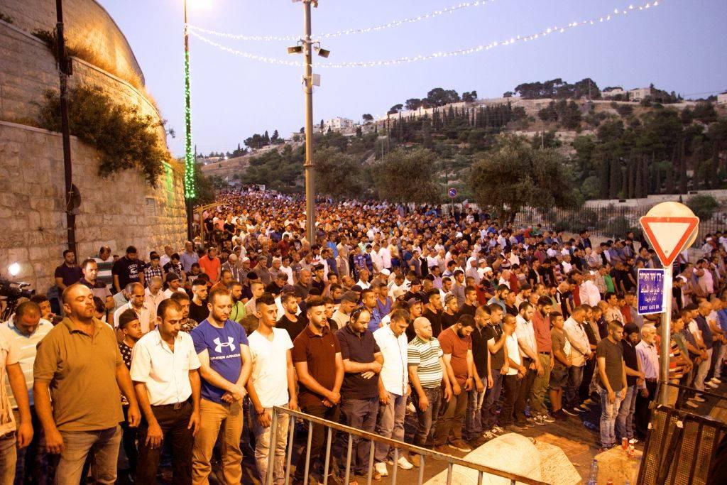 Miles de musulmanes participan en oraciones vespertinas fuera de la Puerta de los Leones en la Ciudad Vieja de Jerusalém, negándose a entrar en el recinto del Monte del Templo para llegar a la Mezquita Al-Aqsa, el 25 de julio de 2017. (Dov Lieber / Times of Israel)