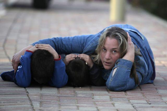 Una mujer israelí junto con sus hijos se colocan en la posición de seguridad ante la ronda de ataques de terroristas de Hamas desde Gaza que llevó a la incursión israelí en Gaza.
