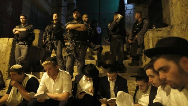 Los policías de frontera mantienen la guardia mientras los fieles oran durante el Tisha B'Av ayunando en una puerta que conduce al edificio del Monte del Templo de la Ciudad Vieja de Jerusalém el 31 de julio de 2017. (AFP Photo / Menahem Kahana)