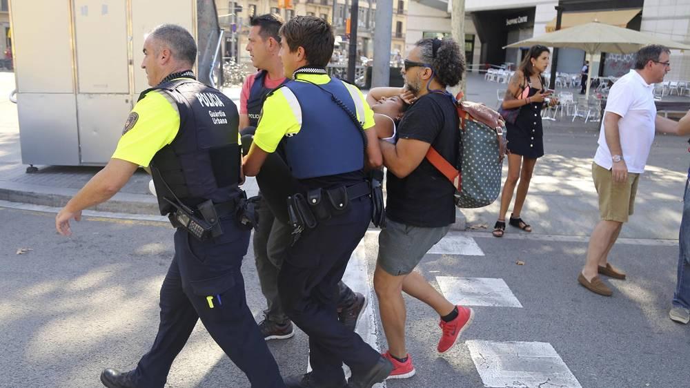 El momento en el que policías llevan a una de las víctimas (AP)