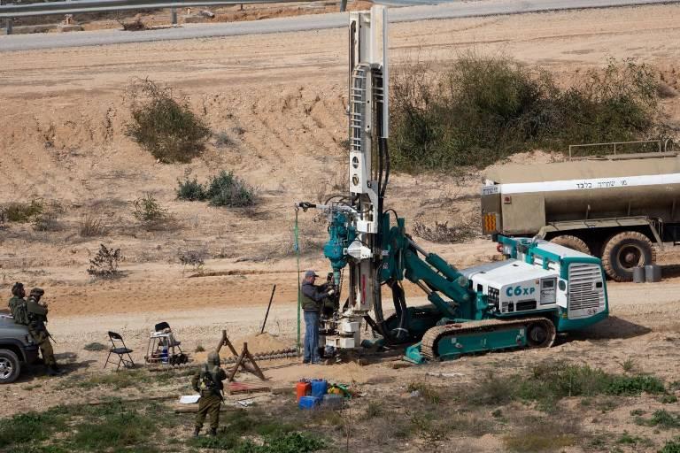 Esta foto de archivo del 10 de febrero de 2016 muestra soldados de las FDI vigilando mientras una máquina perfora pozos en el lado israelí de la frontera con la Franja de Gaza mientras buscan túneles usados por terroristas musulmanes planeando atacar a Israel. (AFP / Menahem Kahana)