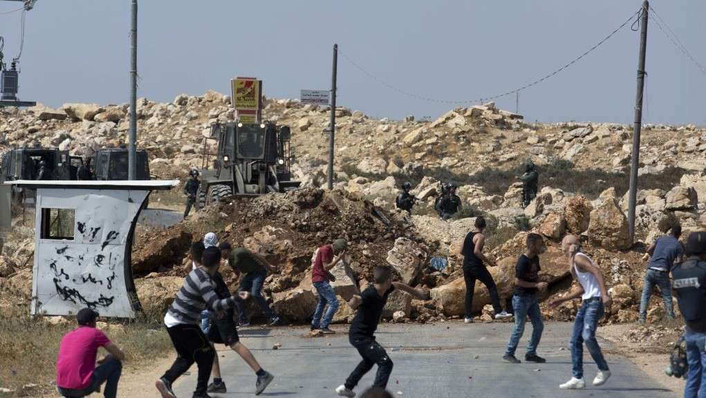 Turbas islámicas lanzan piedras a los soldados israelíes en la aldea de Kobar, mientras una excavadora del ejército cierra la carretera principal hacia la zona durante una operación para preparar la casa de un terrorista para la demolición el 22 de julio de 2017. (AP Photo / Nasser Nasser)