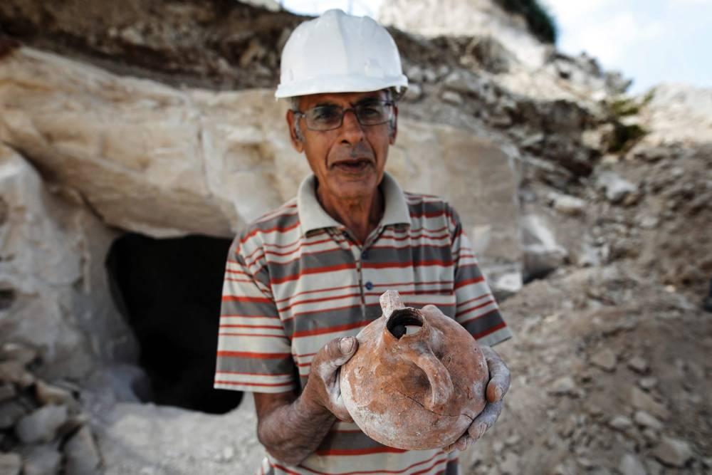 Nashed Abel Halim, excavador arqueológico árabe-israelí, sostiene un antiguo frasco de cerámica descubierto en un sitio de excavación que data del período romano en el pueblo de Reina, cerca de Nazaret, el 10 de agosto de 2017. MENAHEM KAHANA / AFP
