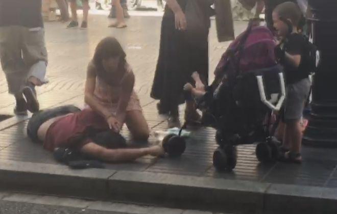 Una mujer atiende a un hombre tendido en la acera. / Christopher Rodríguez