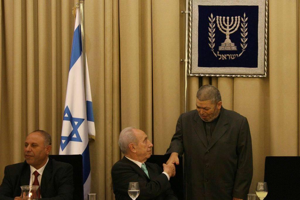 El ex presidente de Israel, Shimon Peres, estrecha la mano con el jeque Abdullah Nimr Darwish (R) durante una comida Iftar en la residencia del presidente en Jerusalém el 9 de septiembre de 2008. (Anna Kaplan / Flash90)