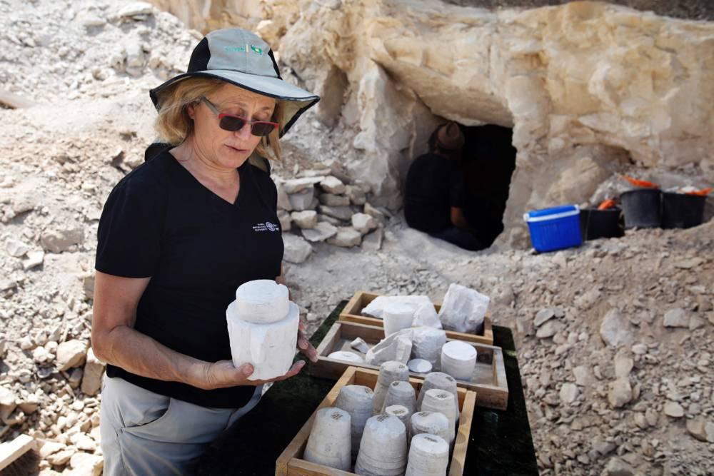 La arqueóloga Yardenna Alexandre inspecciona los núcleos de piedra de cal y las tazas descubiertas en un sitio de excavación que data del período romano en Reineh, el 10 de agosto de 2017. MENAHEM KAHANA / AFP