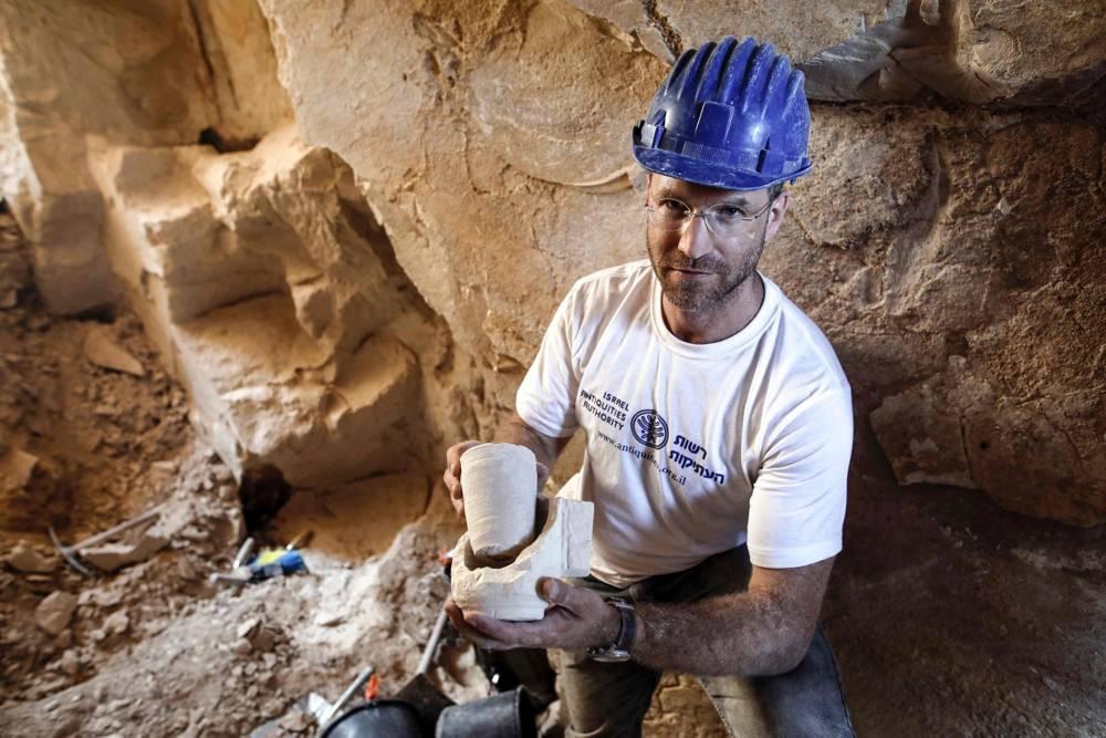 El Dr. Yonatan Adler, director de excavaciones en un sitio que data del período romano, muestra tazones de piedra calcárea y núcleos descubiertos dos meses antes, en el pueblo de Reina, cerca de Nazaret, 10 de agosto de 2017. MENAHEM KAHANA / AFP