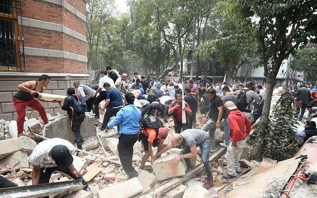 La gente retira los escombros de un edificio dañado después de un terremoto que sacudió la ciudad de México el 19 de septiembre de 2017, momentos después de que se realizó un simulacro de terremoto en la capital. (Foto AFP / Alfredo Estrella)