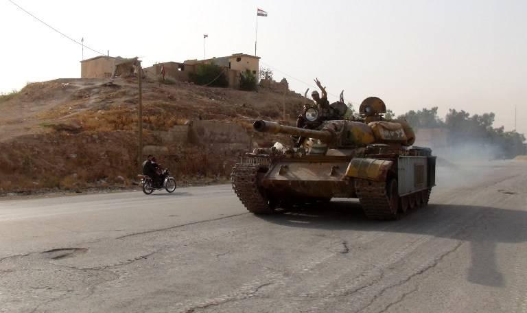 Un combatiente en favor del régimen muestra el signo de la victoria el 21 de agosto de 2016 mientras conduce un tanque en el distrito meridional de Ghweiran en la ciudad de Hasakeh, en el noreste sirio, donde las fuerzas kurdas avanzaban (AFP / STR)
