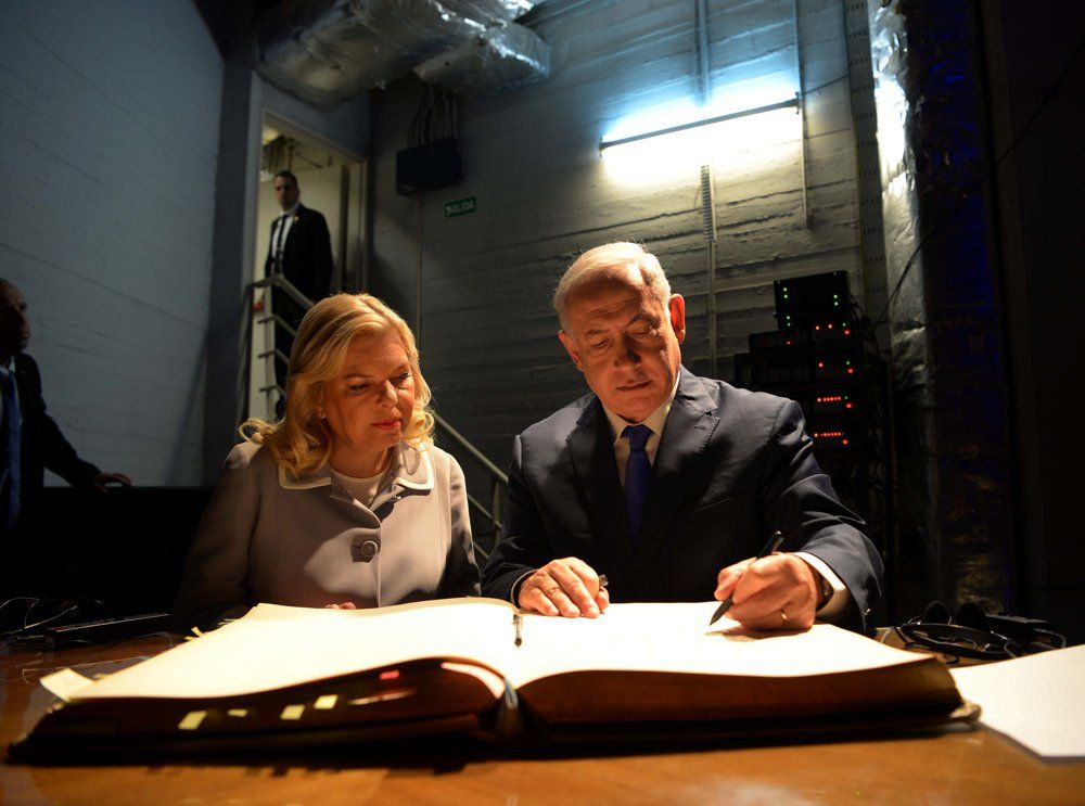 El primer ministro israelí Benjamin Netanyahu y su esposa Sara firman el libro de invitados durante una visita a la embajada de Israel en Buenos Aires, Argentina, el 11 de septiembre de 2017 (Avi Ohayon / GPO)
