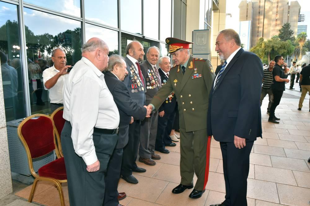 Avigdor Liberman, a la derecha, y el ministro de Defensa ruso, Sergey Shoigu, estrechando la mano de los veteranos en la sede central de Kiria, en Tel Aviv, el 16 de octubre de 2017. (Ariel Hermoni / Ministerio de Defensa)