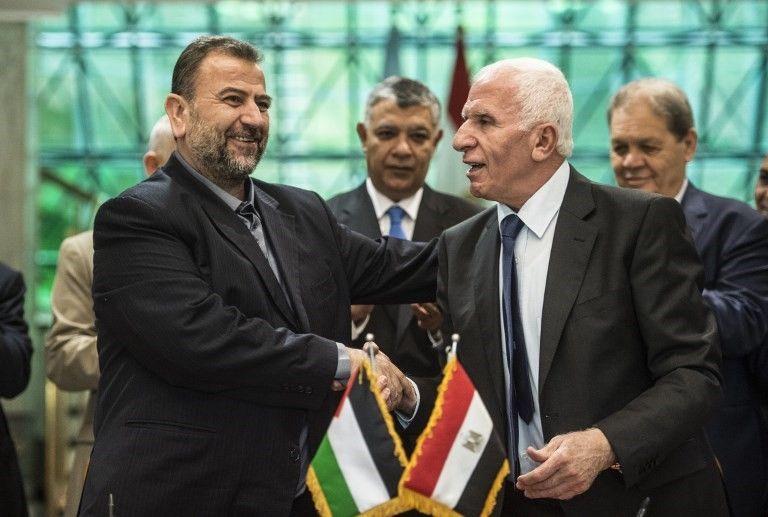 Azzam al-Ahmad, de Fatah (derecha), y Saleh al-Arouri, a la izquierda, de Hamas estrechan la mano después de firmar un acuerdo de reconciliación en El Cairo el 12 de octubre de 2017, cuando los dos movimientos árabes rivales terminaron su década de división tras las negociaciones supervisadas por Egipto . (AFP / Khaled Desouki)