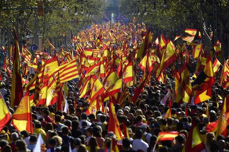 Los manifestantes ondean las banderas Senyera españolas y catalanas durante una manifestación pro unidad en Barcelona el 29 de octubre de 2017. (AFP PHOTO / PIERRE-PHILIPPE MARCOU)