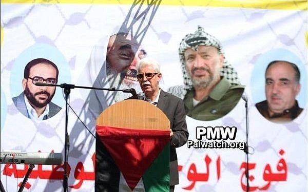El funcionario de Fatah, Jamal Muhaisen, habla frente a una pancarta que alaba a los terroristas árabes como 'héroes' en una recepción de la Universidad Al-Quds para nuevos estudiantes el 15 de octubre de 2017. (Palestinian Media Watch)