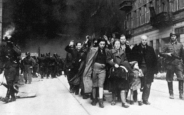 Los judíos en el Gueto de Varsovia son conducidos por soldados alemanes a un punto de reunión para su deportación a los campos de exterminio, 1943. (Dominio público)