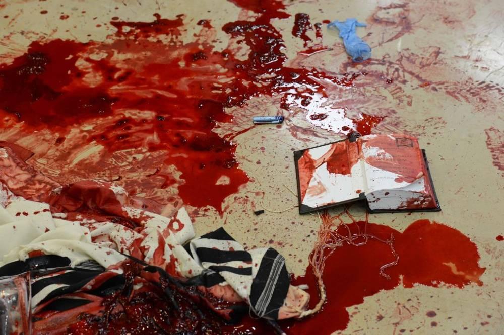 Sangre en los mantos de oración y libros de rezos dentro de la sinagoga Kehilat Yaakov de Har Nof, donde dos terroristas musulmanes atacaron a los fieles rezando, mataron a cuatro y un policía que intentó frustrarlos, el 18 de noviembre de 2014. (Crédito de la foto: Kobi Gideon / GPO / FLASH90)