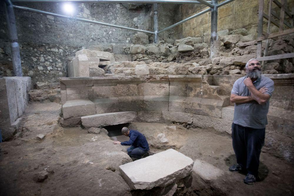 Mientras el arqueólogo Avi Salomón observa, Joe Uziel (L), arqueólogo de la Autoridad de la Antigüedad de Israeñ, limpia piedras en el sitio de una antigua estructura romana parecida a un teatro que estuvo escondida durante 1,700 años en los túneles del Muro Occidental debajo de la Ciudad Vieja de Jerusalém en octubre 16, 2017. (Yonatan Sindel / Flash 90)