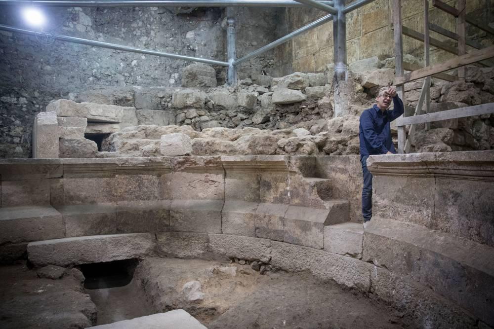 Joe Uziel, arqueólogo de la Autoridad de Antigüedades de Israel, limpia piedras en el sitio de una antigua estructura romana parecida a un teatro, escondida durante 1.700 años, junto al Muro Occidental debajo de la Ciudad Vieja de Jerusalém el 16 de octubre de 2017 (Yonatan Sindel / Flash90)