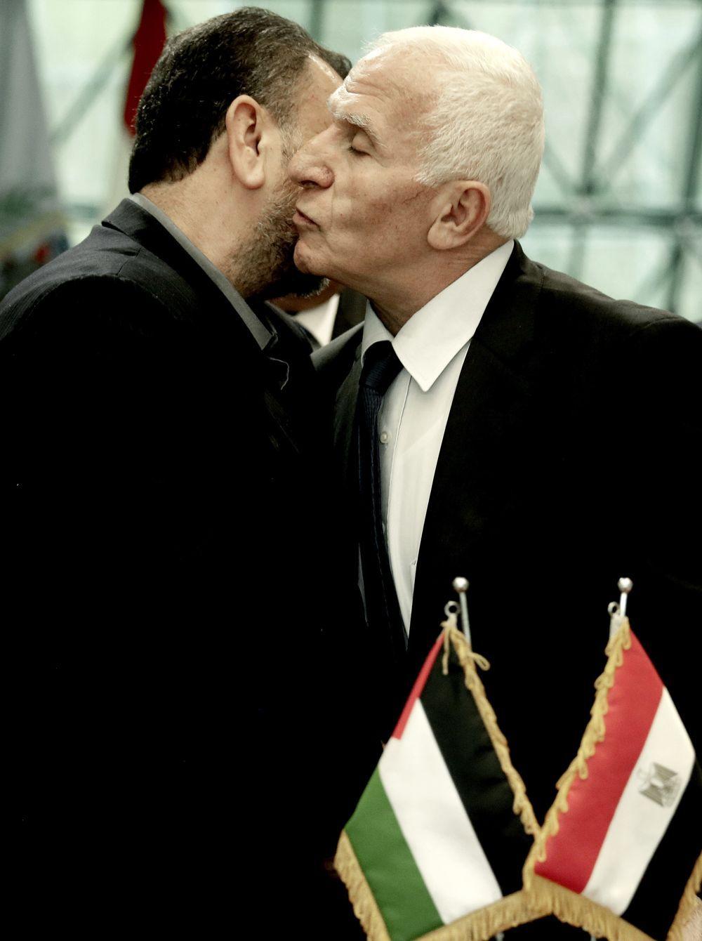 El funcionario de Fatah, Azzam al-Ahmad, y el representante de Hamas, Saleh al-Arouri, se besan después de firmar un acuerdo de reconciliación en una ceremonia corta en el complejo egipcio de inteligencia en El Cairo, Egipto, jueves 12 de octubre. Foto / Nariman El-Mofty)