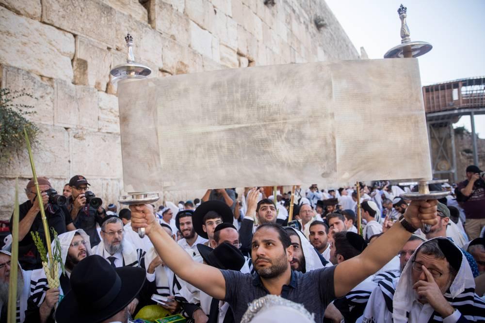 Judíos sostienen el rollo de la Torá en la bendición sacerdotal anual durante la festividad de Sukkot en el Muro Occidental en la Ciudad Vieja de Jerusalén el 8 de octubre de 2017. (Yonatan Sindel / Flash90)