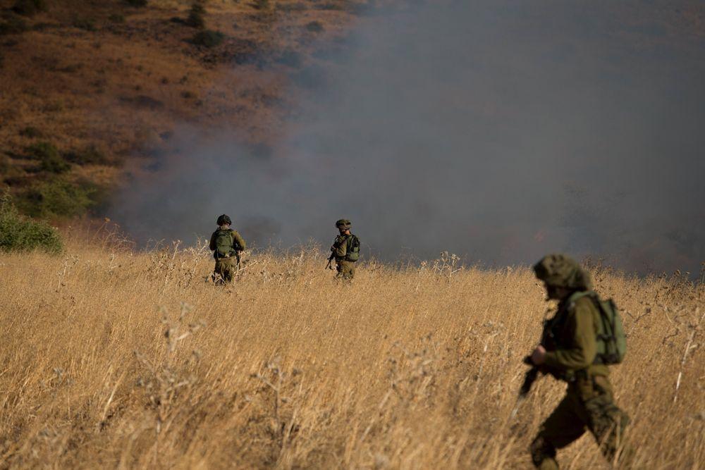 Soldados israelíes buscan en la zona del impacto de un proyectil procedente de Siria