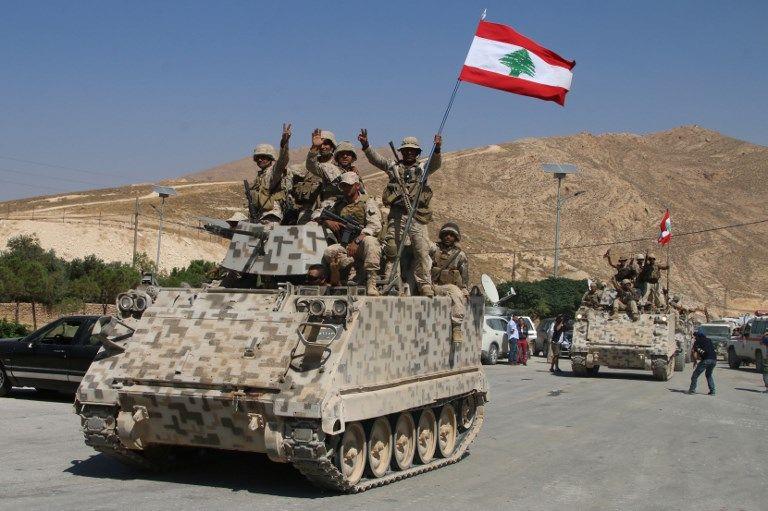 Soldados libaneses se sientan sobre un transportador de personal blindado en la ciudad oriental de Ras Baalbek el 21 de agosto de 2017, después de regresar de la lucha contra el Estado Islámico. (AFP Photo / Stringer)