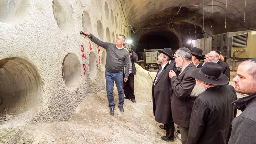 El director general de Rolzur, Arik Glazer, da al Gran Rabino de Israel, David Lau y a otros, un recorrido por el cementerio subterráneo en construcción en Jerusalem. (Cortesía de Rolzur)