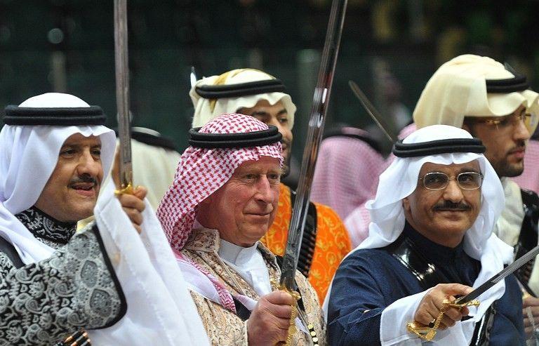 """El príncipe Carlos (C) de Gran Bretaña viste un uniforme saudita tradicional cuando participa en un baile de espada """"Ardah"""" en Arabia Saudita en 2014. (AFP / Pool / Fayez Nureldine)"""