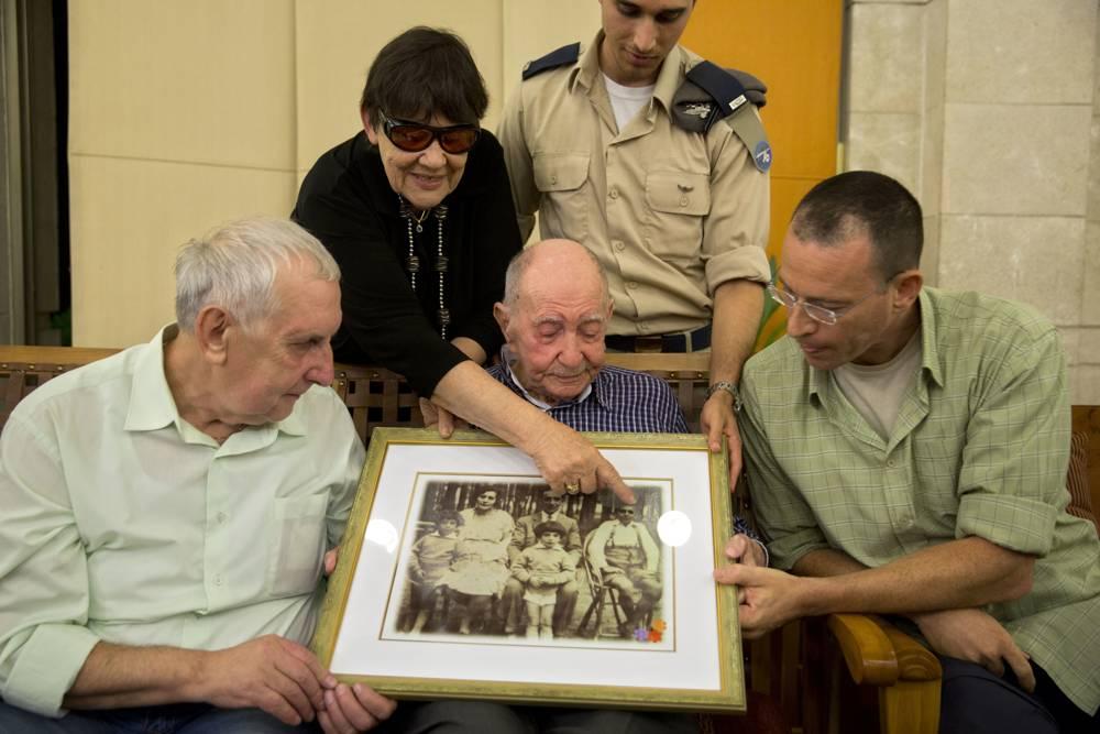 El sobreviviente del Holocausto Eliahu Pietruszka, en el centro, mira una fotografía con Alexandre Pietruszka y su familia en Kfar Saba, 16 de noviembre de 2017. (AP / Sebastian Scheiner)