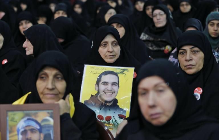 Una foto tomada el 10 de noviembre de 2017 muestra a los familiares de los combatientes de Hezbolá que murieron en combate en Siria, portando los retratos de sus familiares durante una reunión en el suburbio sureño de Beirut. (Anwar Amro / AFP)