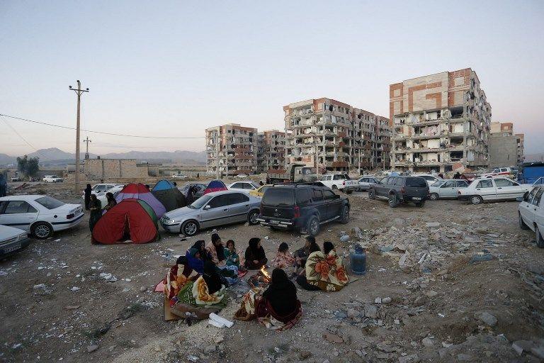 Los residentes se amontonan junto a un fuego en un área abierta después de un terremoto de magnitud 7.3 en Sarpol-e Zahab en la provincia iraní de Kermanshah el 13 de noviembre de 2017. (AFP / ISNA / POURIA PAKIZEH)