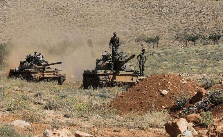 Una foto tomada el 26 de julio de 2017 durante un recorrido guiado por el movimiento libanés chiita Hezbollah muestra a soldados sirios montados en un tanque cerca de combatientes de Hezbollah en una zona montañosa alrededor de la ciudad libanesa de Arsal a lo largo de la frontera con Siria. (AFP PHOTO / ANWAR AMRO)