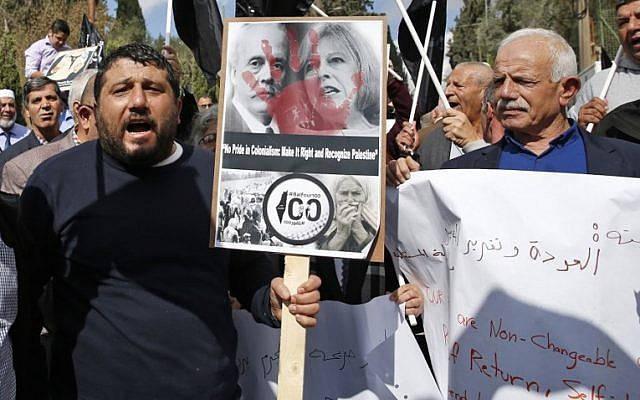 Manifestantes musulmanes sostienen un póster mientras se reúnen frente al Consulado británico en el este de Jerusalén, el 2 de noviembre de 2017, para protestar en el centenario de la Declaración Balfour de Gran Bretaña, que ayudó a la creación del Estado de  Israel. (AHMAD GHARABLI / AFP)