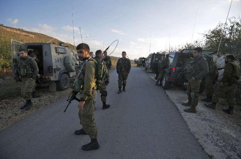 Soldados israelíes cierran una carretera cerca de la frontera en los Altos del Golán para evitar que los residentes drusos crucen a Siria después de un atentado suicida en la aldea siria drusa de Hader el 3 de noviembre de 2017. (Jalaa Marey / AFP)